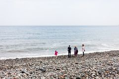 The family is walking along the beach by the sea. Wind on the seashore with people walking on the beach. Rocky beach by the sea. F stock photos