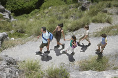 Family Walking Along Mountain Path Stock Photo
