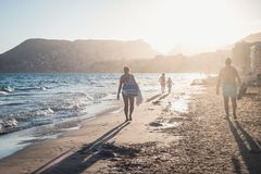 Family walking along the ocean in the sunset. Mom, dad and two kids running on the beach, sunset time, mountains on background in Calpe, Spain Royalty Free Stock Photo