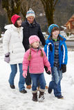 Family Walking Along Snowy Street In Ski Resort Stock Photo
