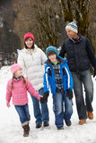 Family Walking Along Snowy Street In Ski Resort Royalty Free Stock Photos