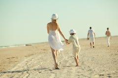 Family Walking Along The Beach Royalty Free Stock Photos