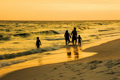 Family Walking Along Together on a Florida Beach at Sunset. A family of four walking along a beach in Florida during sunset on a warm summer night. The mom and Royalty Free Stock Photography