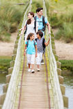 Family Walking Along Wooden Bridge royalty free stock images