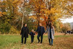 Family walking in an autumn forest with fallen leaves. Mother father and two daughters in the park royalty free stock photos