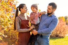 Family walking in autumn park at sunset royalty free stock photography