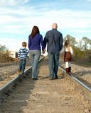 Family Walking Away. Family of four holding hands and walking away from the camera on railroad tracks royalty free stock photo