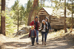 Family walking away from a log cabin in a forest Royalty Free Stock Photography