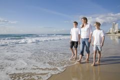 Family walking on the beach Stock Photos