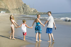Family walking on beach royalty free stock photography