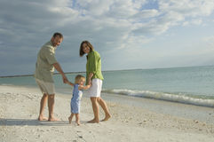 Family walking on beach royalty free stock photos