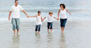 Family walking on the beach Stock Photo