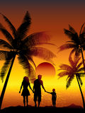 Family walking on beach. Silhouettes of a family walking on a tropical beach Stock Image