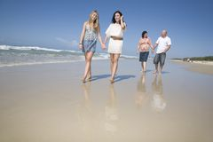 Family walking on beach holding hands Stock Photos