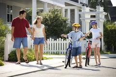 Family Walking with Bicycles. Family of four walking together on sidewalk with bicycles stock photography