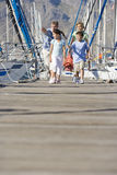 Family walking in boat marina Royalty Free Stock Images