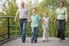 Family walking on bridge in early fall park. Family with two children walking on bridge in early fall park. family is handies. focus on little boy Royalty Free Stock Image