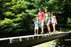 Family walking on the bridge in forest Royalty Free Stock Photos