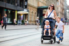 Family walking in city center. Young mother with her son and toddler daughter in stroller walking in city center Stock Photos