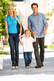 Family walking with dog in city street Stock Image