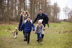 Family walking dog together in the countryside, front view Royalty Free Stock Images