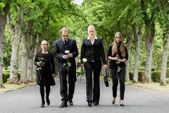 Family walking down alley at graveyard. Family on cemetery walking down alley at graveyard with roses Stock Photography