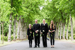 Family walking down alley at graveyard. Family on cemetery walking down alley at graveyard with roses Stock Photos
