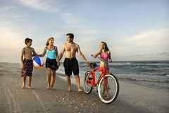 Family walking down the beach. Caucasian family of four walking on beach Stock Images