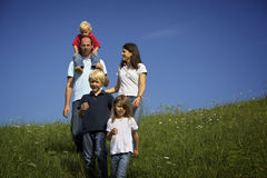 Family walking in field. Happy family of five walking in field Stock Photography
