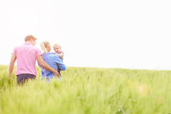 Family Walking In Field Carrying Young Baby Son Royalty Free Stock Photography
