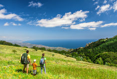 Family walking on field. Happy family walking with backpacks on field and looking at the sea Royalty Free Stock Photos