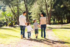 Family walking forest. Rear view of young family walking in forest Stock Photo