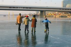 Family walking on ice. Happy family taking a walk on the frozen river danube royalty free stock image