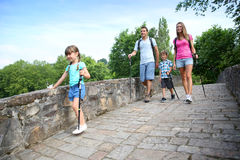 Family on walking journey. Family on a rambling journey crossing roman bridge Stock Photo