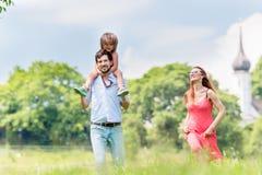 Family walking on meadow having walk Royalty Free Stock Photo