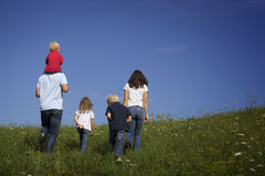 Family walking in meadow, view from behind.