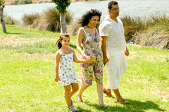 Family walking outdoors. Holding hands and smiling Royalty Free Stock Photo