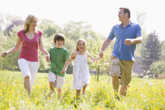 Family walking outdoors holding hands smiling Stock Photo