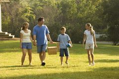 Family walking in park. Caucasian family of four walking in park carrying picnic basket Royalty Free Stock Images