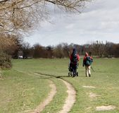 Family Walking in a Park. A Couple pushing a Pushchair Walking along a footpath in an English Park Stock Photos