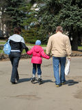 Family walking in a park. With girl on rolling skates royalty free stock photography