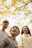 Family walking through the park in the autumn, low angle view Royalty Free Stock Photos