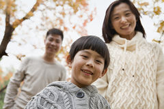 Family walking through the park in the autumn, portrait Royalty Free Stock Photo