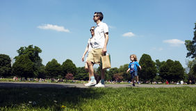 Family walking in a park under the blue sky Royalty Free Stock Photo