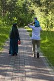 A family is walking in the park - a woman in a hijab, a man carrying a child on his shoulders.  Back view. stock photo