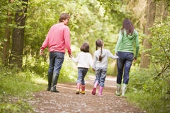 Family walking on path holding hands. From the back Stock Photography