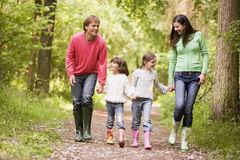 Family walking on path holding hands smiling.  Royalty Free Stock Images