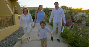 Family walking on resort area in the evening stock video footage