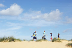 Family Walking Sand Dune On Beach Stock Photo