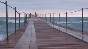 Family are walking at the sea pier in storm. Waves splashes through the wooden pier in the sea. Beautiful seascape in. Sunset stock footage